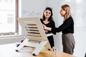 Two women standing in front of a standing desk. One woman is pointing and the other is listening.